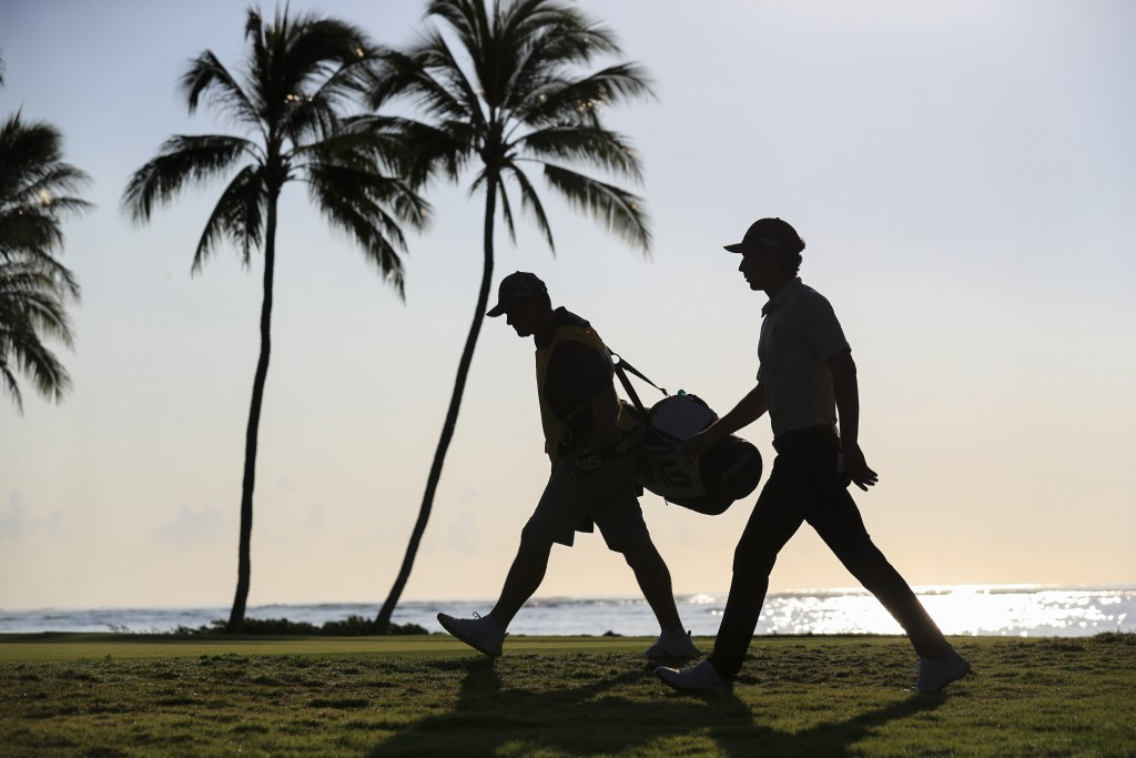 Joaquin Niemann, right, of Chile, walks from the 11th green with caddie Gary Matthews during the second round of the Sony Open golf tournament Friday,...