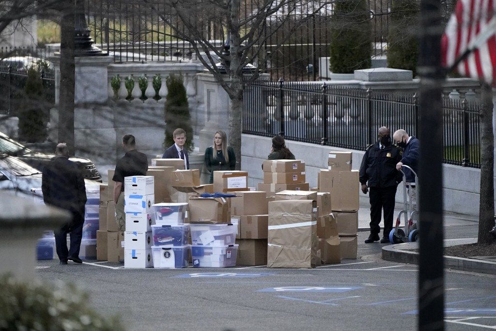 FILE - In this Jan. 14, 2021, file photo people wait for a moving van after boxes were moved out of the Eisenhower Executive Office building inside th...
