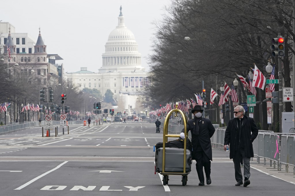 Danish Rozario, left, of Silver Spring, Md., wheels baggage down Pennsylvania Avenue for a guest at the Trump Hotel in Washington, Friday, Jan. 15, 20...