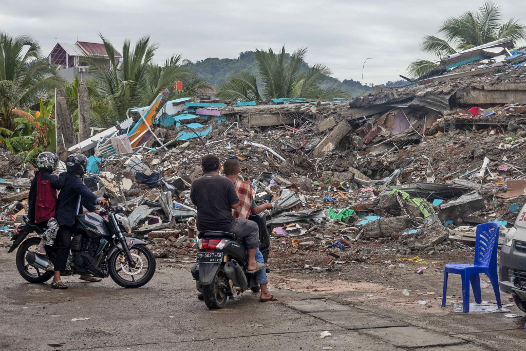 People look at the ruin of a building flattened during an earthquake in Mamuju, West Sulawesi, Indonesia, Saturday, Jan. 16, 2021. Damaged roads and b...