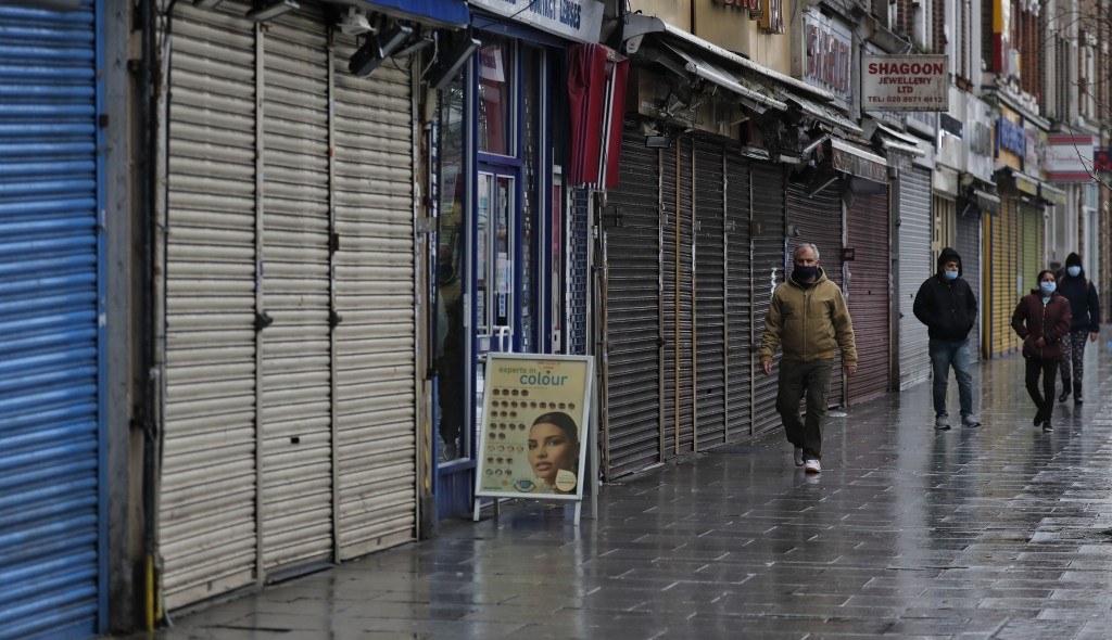 People walk past closed stores in London, Saturday, Jan. 16, 2021, during England's third national lockdown since the coronavirus outbreak began. The ...
