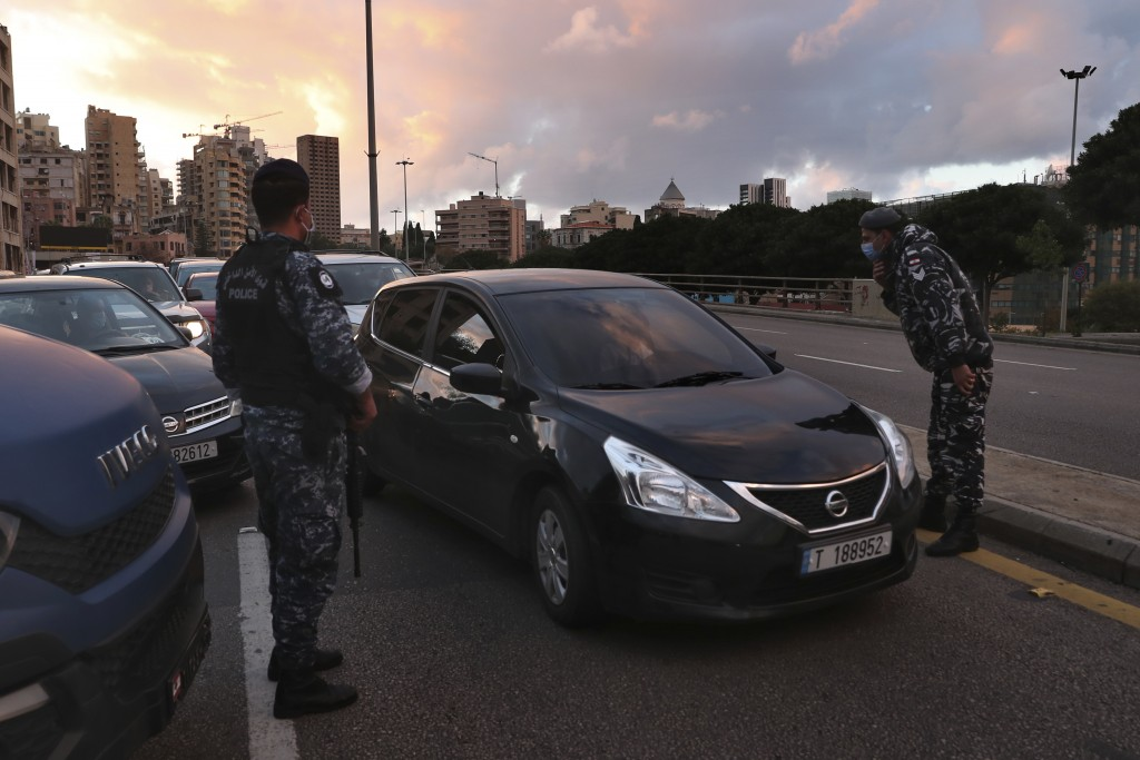 Police officers stand at a checkpoint to inspect cars that violate the lockdown during an 11-day nationwide shutdown aimed at curbing the spread of th...