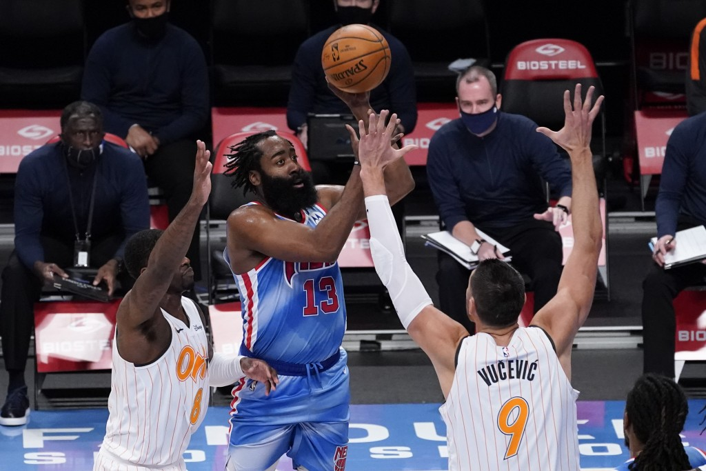 Brooklyn Nets guard James Harden, center, shoots past Orlando Magic forward Dwayne Bacon, left, and center Nikola Vucevic, right, during the first hal...