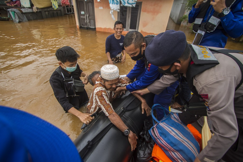 Rescuers assist an elderly man to climb into their boat at a flooded village in Banjar, South Kalimantan on Borneo Island, Indonesia, in this Saturday...
