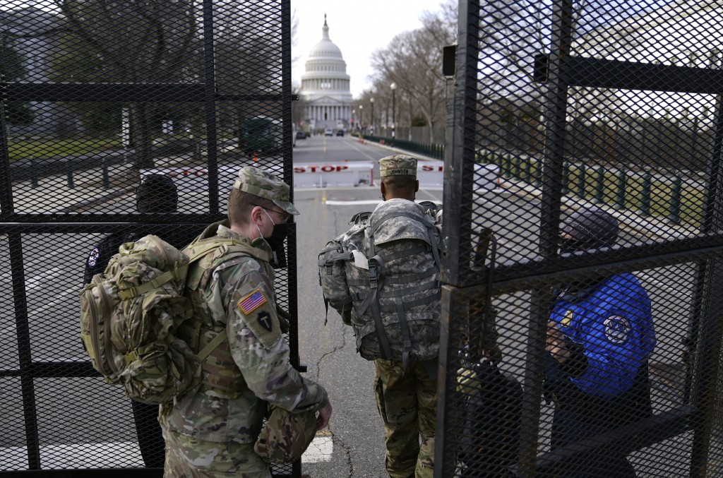 With the U.S. Capitol in the background, troops are let through a security gate on Saturday, Jan. 16, 2021, in Washington as security is increased ahe...