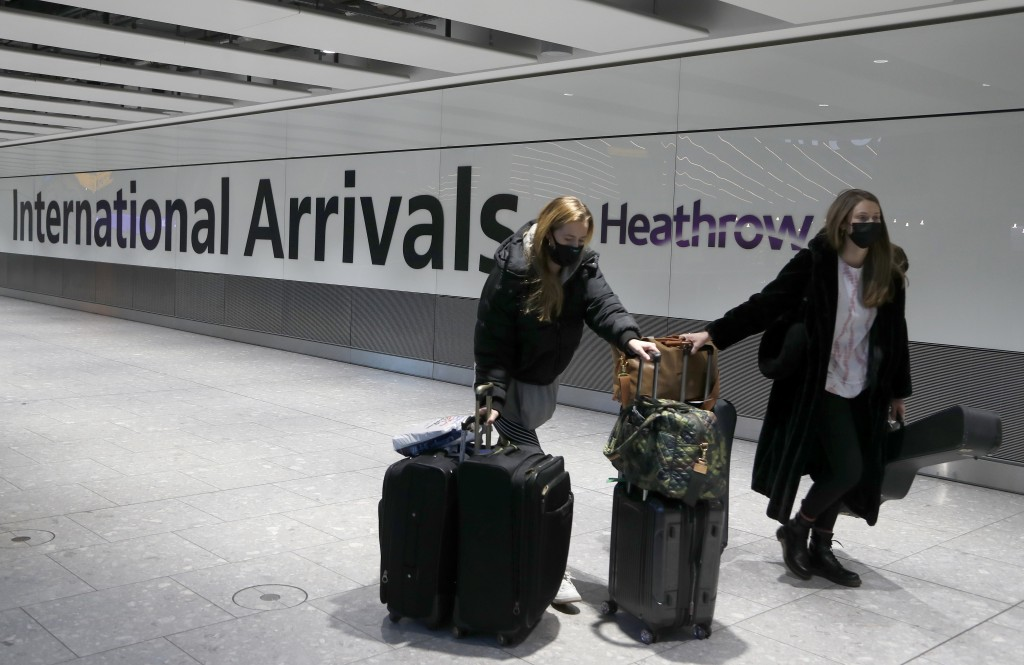 Travellers arrive at Heathrow Airport in London, Sunday, Jan. 17, 2021. The UK will close all travel corridors from Monday morning to protect against ...