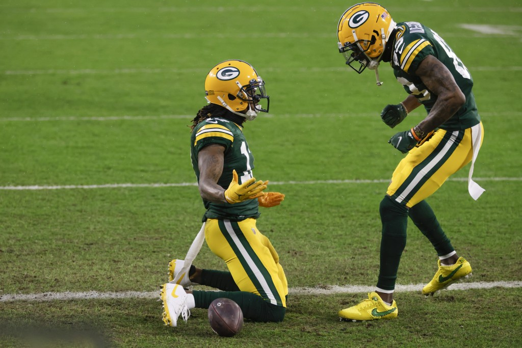 Green Bay Packers' Davante Adams, left, celebrates after scoring with Marquez Valdes-Scantling after a touchdown during the first half of an NFL divis...