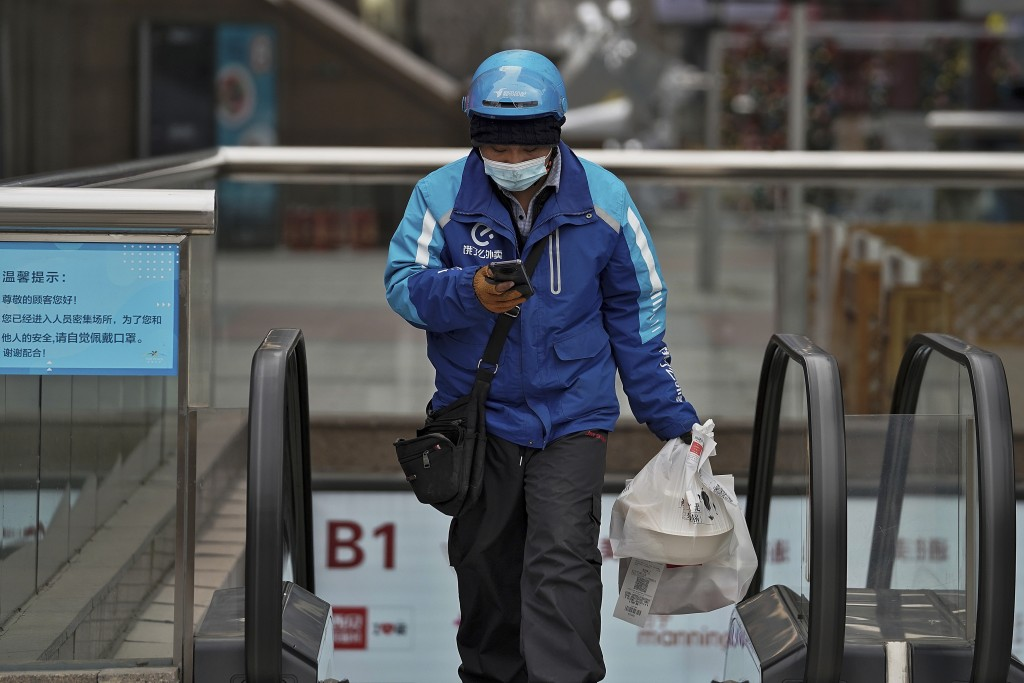 A food delivery worker wearing a face mask to help curb the spread of the coronavirus prepares to deliver foods for his customers at a shopping mall i...