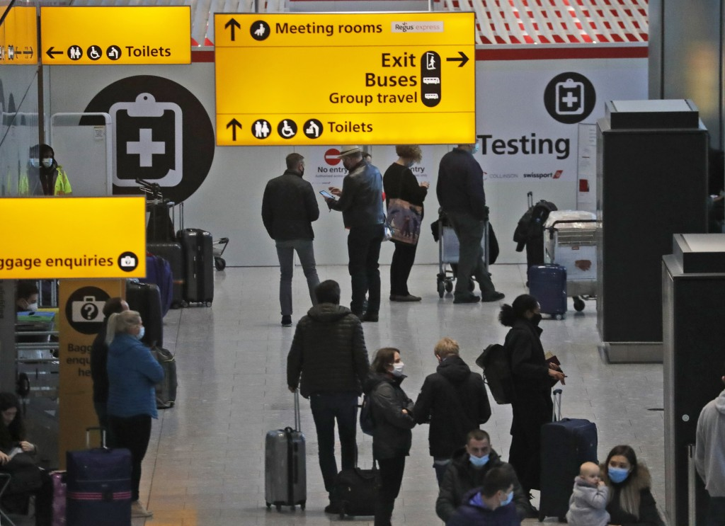Travellers wait at the Covid-19 testing facility at Heathrow Airport in London, Sunday, Jan. 17, 2021.  The UK will close all travel corridors from Mo...