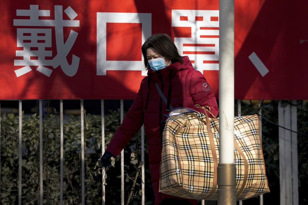 """A woman wearing a face mask to help curb the spread of the coronavirus walks by a banner baring the words """"Wear mask"""" on a street in Beijing, Sunday, ..."""