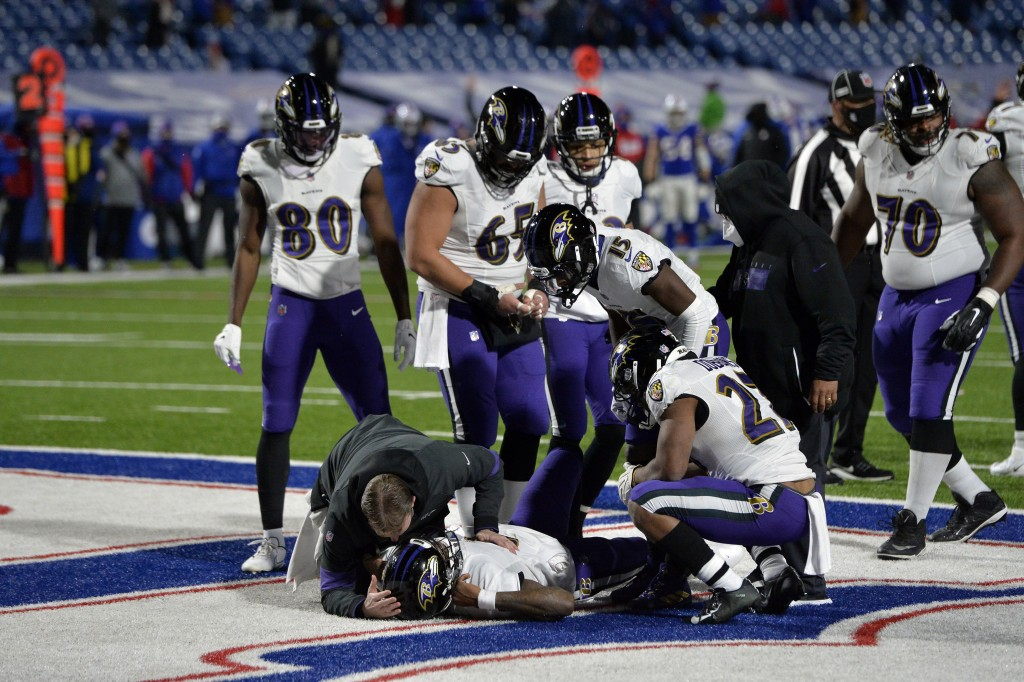A trainer checks on Baltimore Ravens quarterback Lamar Jackson, below, after he was injured during the second half of an NFL divisional round football...