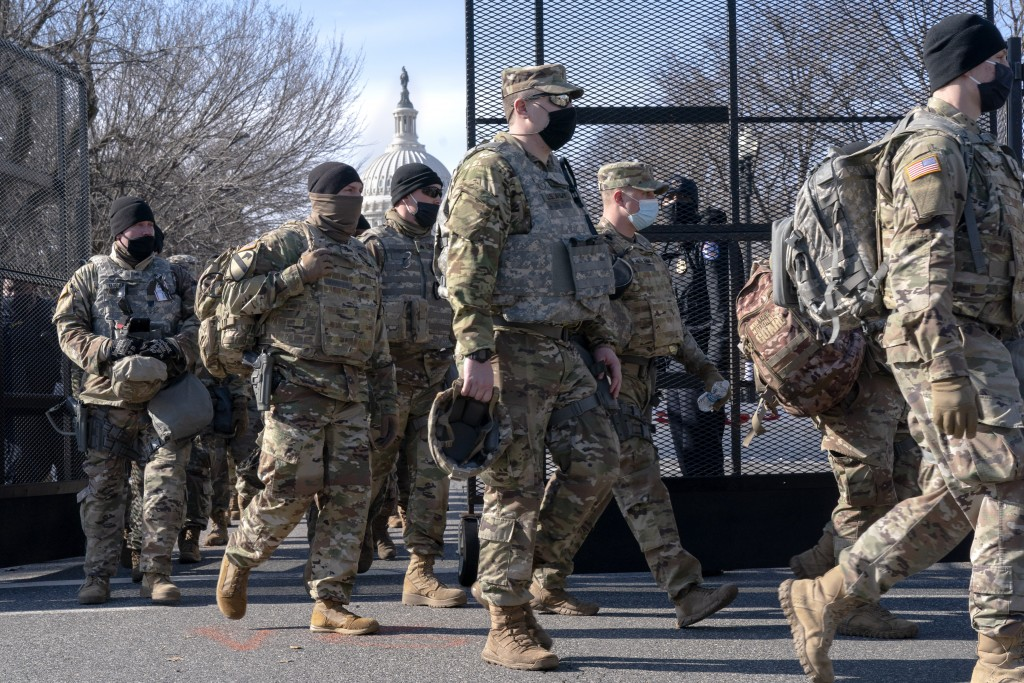 With the U.S. Capitol in the background, members of the National Guard change shifts as they exit through anti-scaling security fencing on Saturday, J...