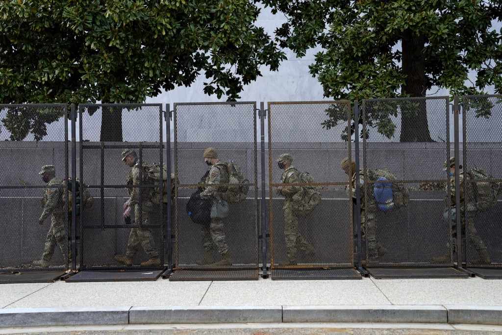Troops walk behind security fencing on Saturday, Jan. 16, 2021, in Washington as security is increased ahead of the inauguration of President-elect Jo...