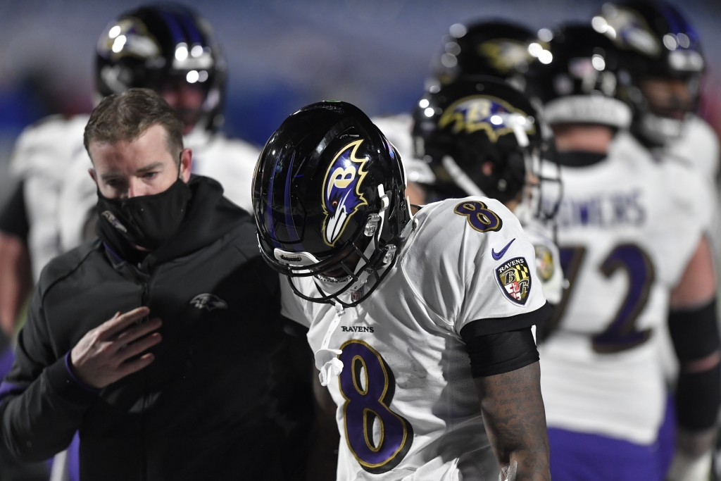 Baltimore Ravens quarterback Lamar Jackson (8) is helped off the field after he was injured during the second half of an NFL divisional round football...