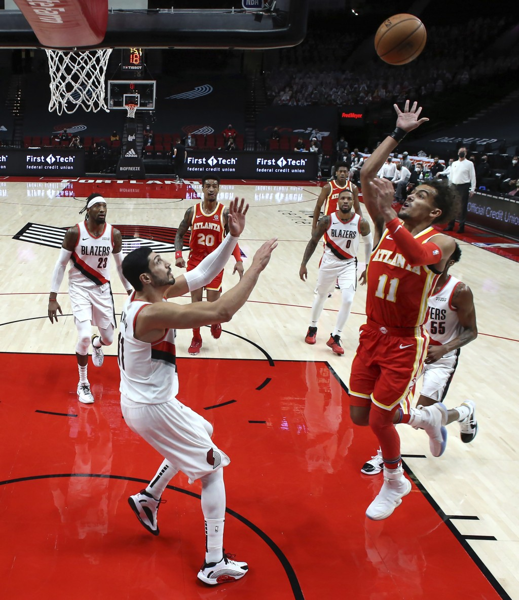 Atlanta Hawks guard Trae Young, right, shoots over Portland Trail Blazers center Enes Kanter during the first half of an NBA basketball game in Portla...