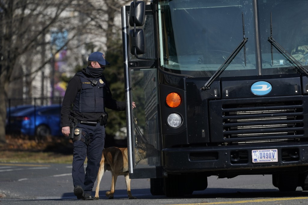 A bomb sniffing dog goes around a bus full of National Guard troops after it arrived at the Capitol, Saturday, Jan. 16, in Washington ahead of the ina...