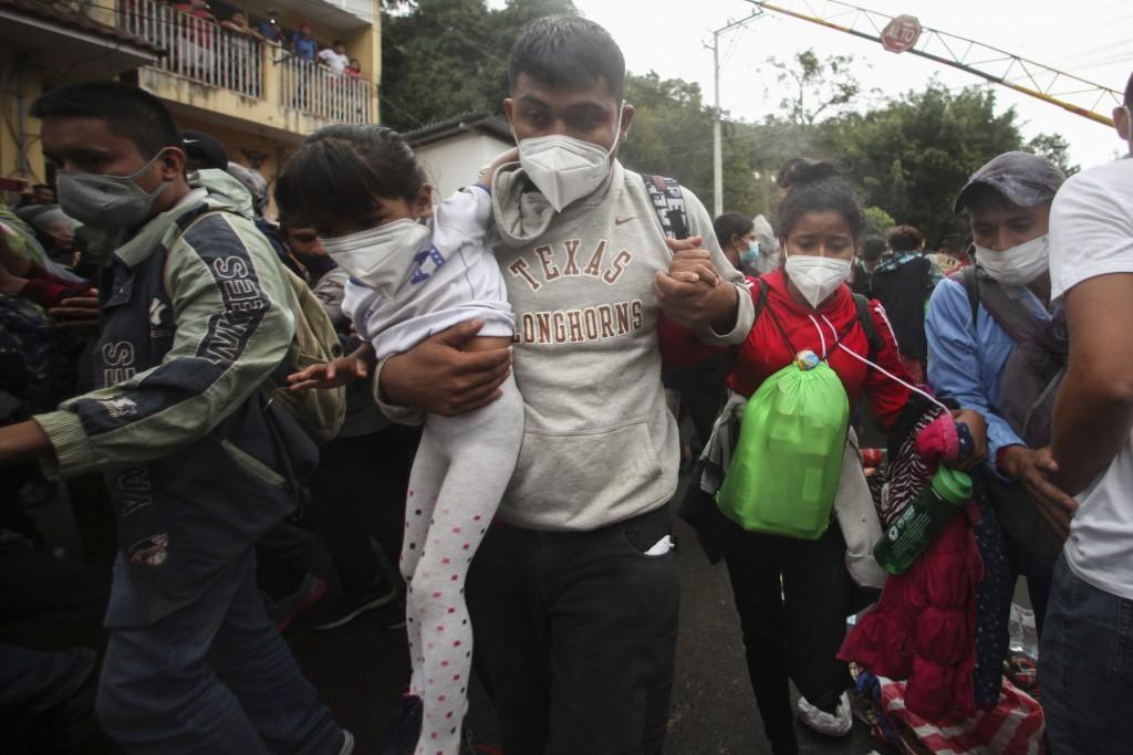 Honduran migrants hoping to reach the U.S. cross the border patrolled by Guatemalan soldiers, in El Florido, Guatemala, Saturday, Jan. 16, 2021. The m...