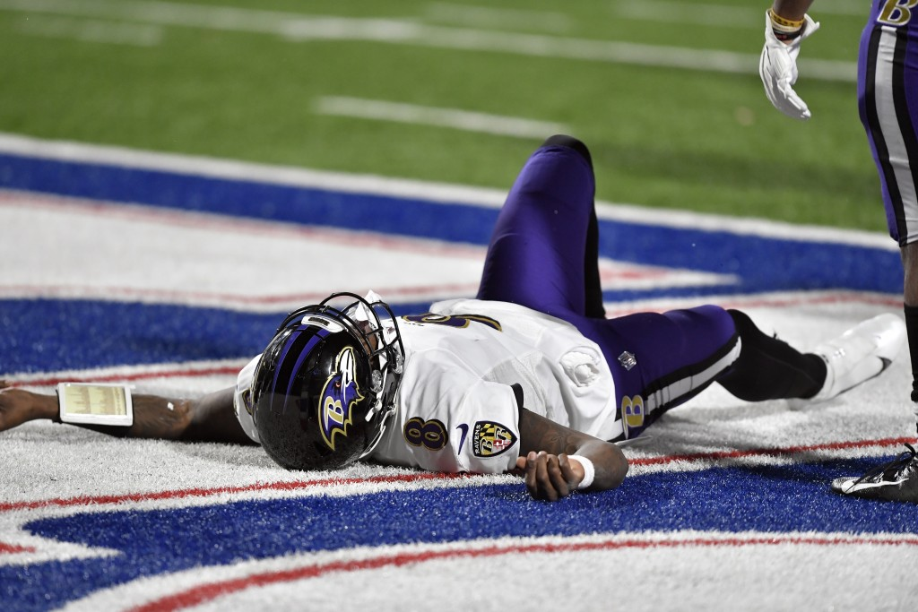 Baltimore Ravens quarterback Lamar Jackson (8) lies on the ground after being injured during the second half of an NFL divisional round football game ...