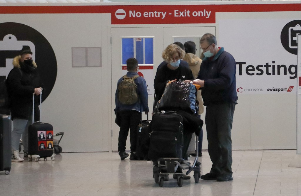 Travellers wait at the Covid-19 testing facility at Heathrow Airport in London, Sunday, Jan. 17, 2021. The UK will close all travel corridors from Mon...