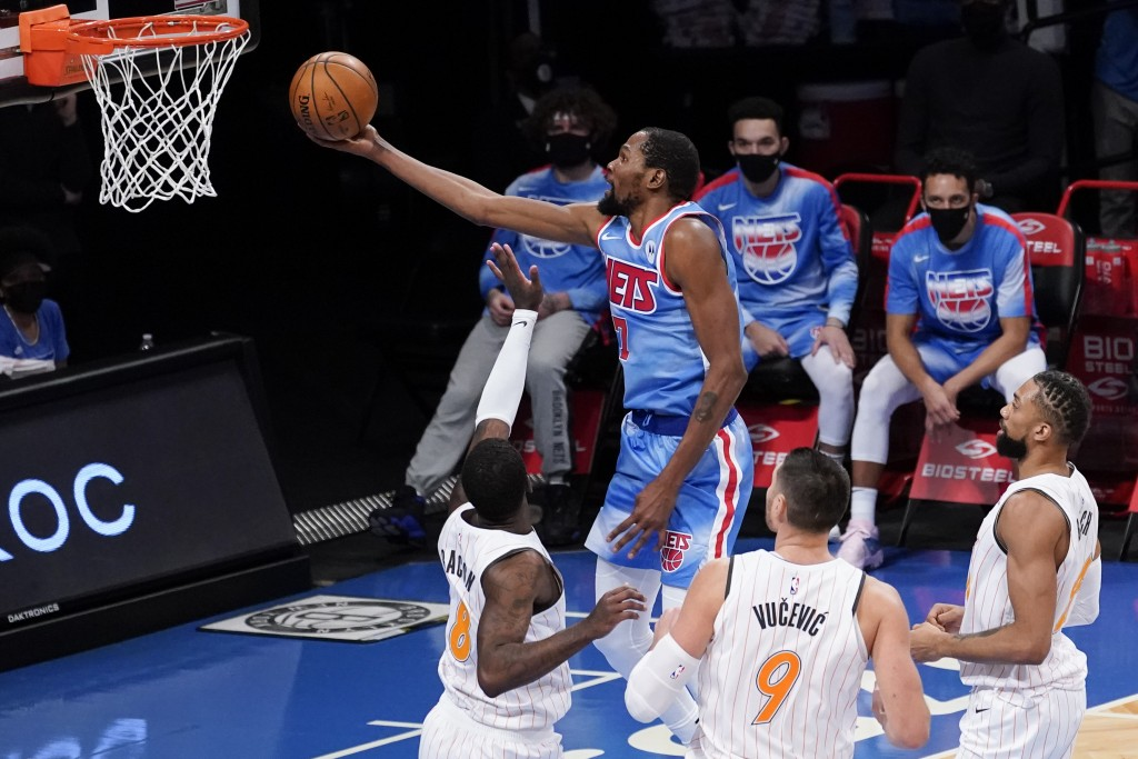 Brooklyn Nets forward Kevin Durant (7) goes to the basket past Orlando Magic forward Dwayne Bacon (8) center Nikola Vucevic (9) and center Khem Birch ...