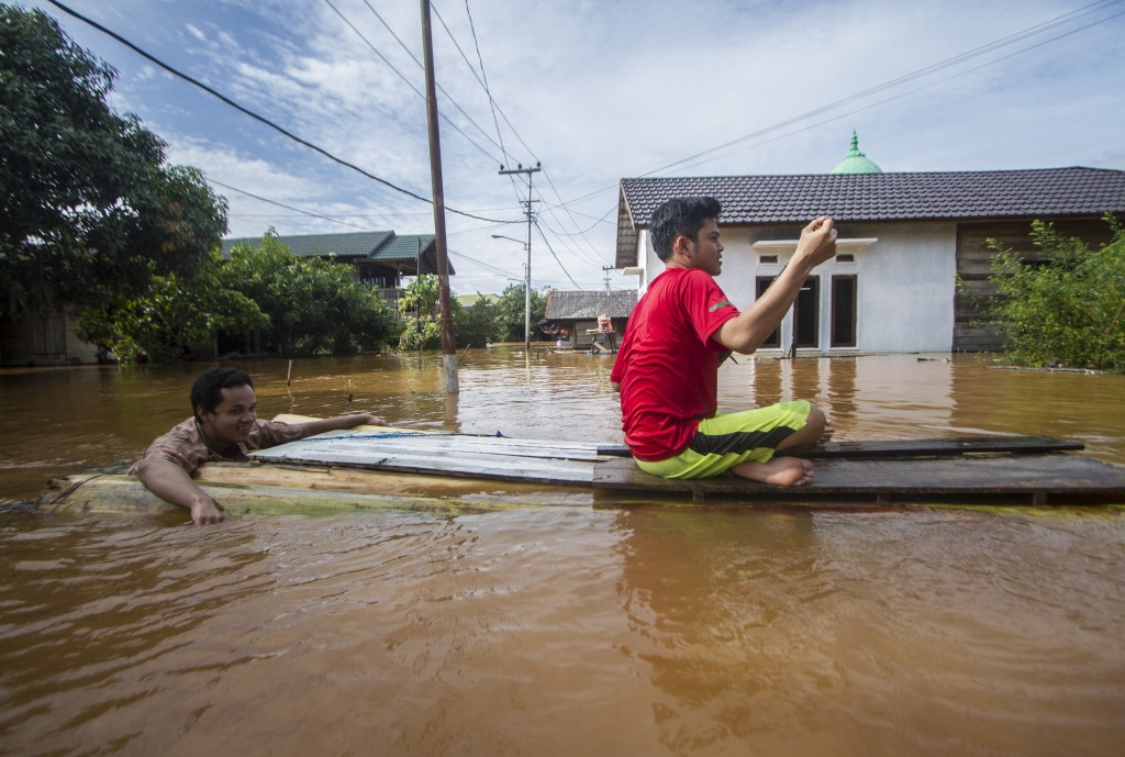 People use a makeshift raft to cross through a flooded village in Banjar, South Kalimantan on Borneo Island, Indonesia, in this Saturday, Jan. 16, 202...