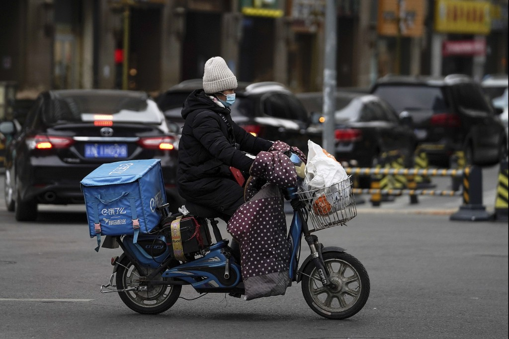 A food delivery worker wearing a face mask to help curb the spread of the coronavirus rides on a street in Beijing on Thursday, Jan. 14, 2021. The e-c...