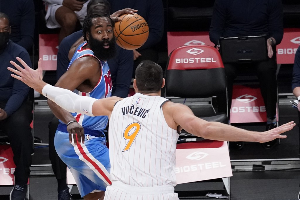 Orlando Magic center Nikola Vucevic, right, guards Brooklyn Nets guard James Harden, left, during the first half of an NBA basketball game, Saturday, ...