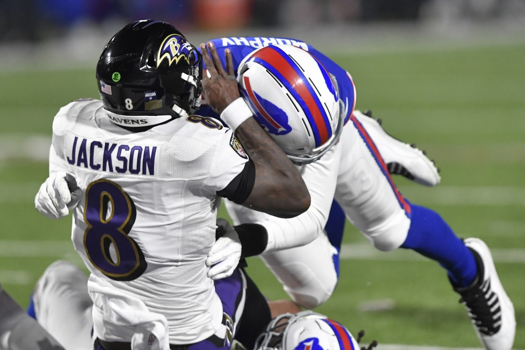 Baltimore Ravens quarterback Lamar Jackson (8) is hit by Buffalo Bills' Trent Murphy (93) during the second half of an NFL divisional round football g...