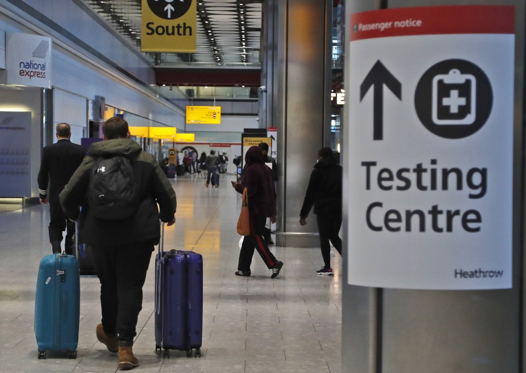 Travellers walk towards the Covid-19 testing centre at Heathrow Airport in London, Sunday, Jan. 17, 2021. The UK will close all travel corridors from ...