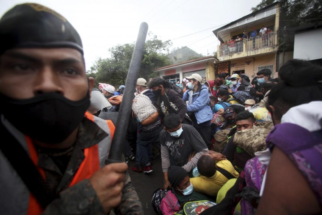 Honduran migrants hoping to reach the U.S. cross the border patrolled by Guatemalan soldiers, in El Florido, Guatemala, Saturday, Jan. 16, 2021. Hondu...