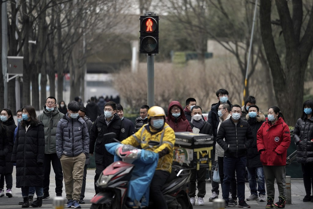 A food delivery worker and office workers wearing face masks to protect themselves from the coronavirus wait to cross a street in Beijing on Thursday,...