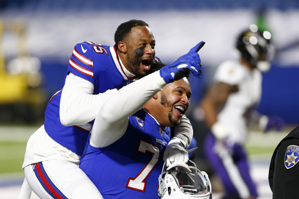 Buffalo Bills' Taiwan Jones (25) celebrates with Dion Dawkins (73) after an NFL divisional round football game against the Baltimore Ravens Saturday, ...