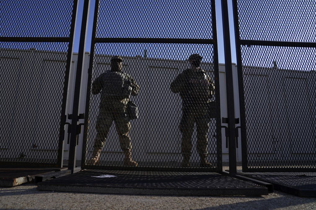 National Guard members stand behind a fence near the U.S. Capitol on Saturday, Jan. 16, 2021, in Washington as security is increased ahead of the inau...