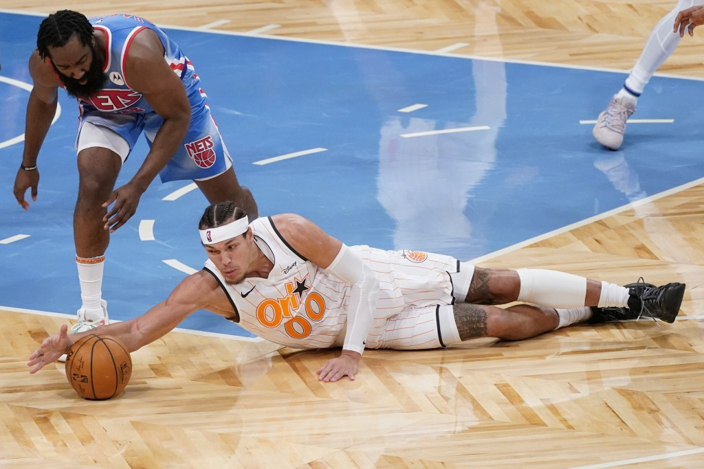 Brooklyn Nets guard James Harden (13) and Orlando Magic forward Aaron Gordon (00) vie for a loose ball during the first half of an NBA basketball game...