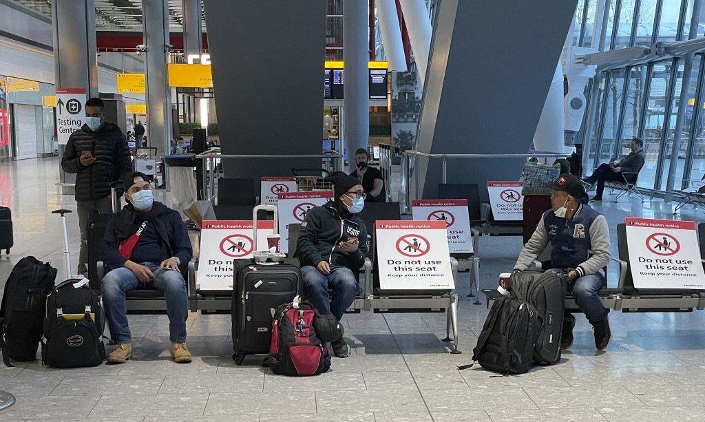 Travellers wait for their Covid-19 test results at Heathrow Airport in London, Sunday, Jan. 17, 2021.  The UK will close all travel corridors from Mon...