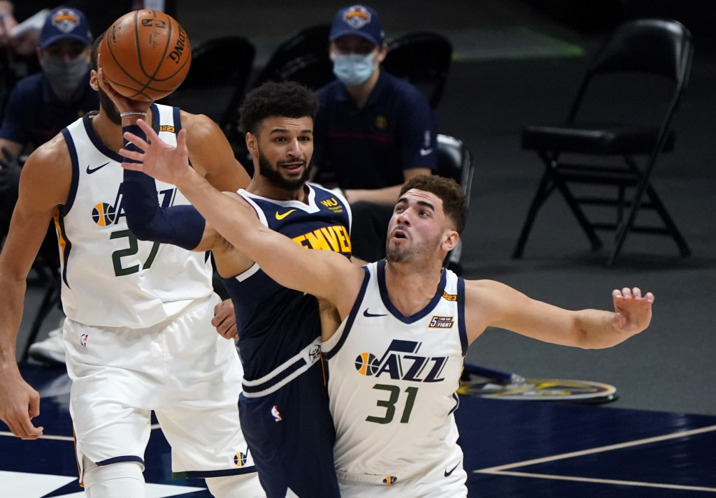 Utah Jazz forward Georges Niang, right, fouls Denver Nuggets guard Jamal Murray, center, while pursuing the ball in the first half of an NBA basketbal...