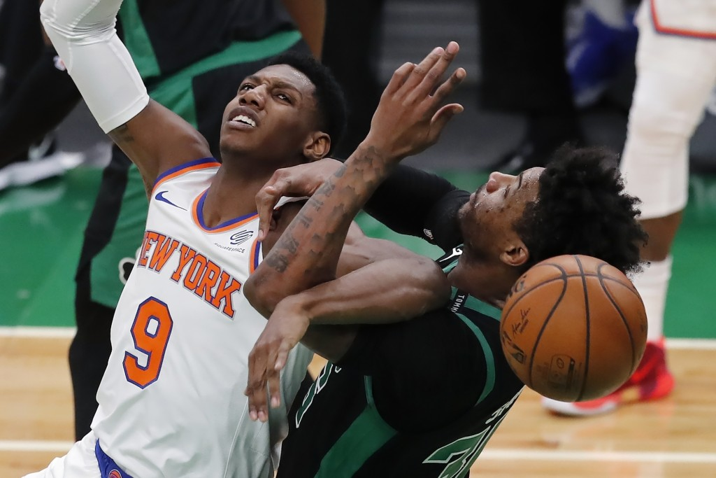 New York Knicks' RJ Barrett (9) and Boston Celtics' Marcus Smart (36) battle for the ball during the first half of an NBA basketball game, Sunday, Jan...
