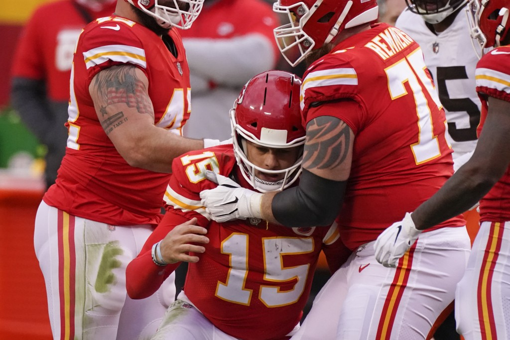 Kansas City Chiefs quarterback Patrick Mahomes (15) is helped off the field by teammate Mike Remmers, right, after getting injured during the second h...