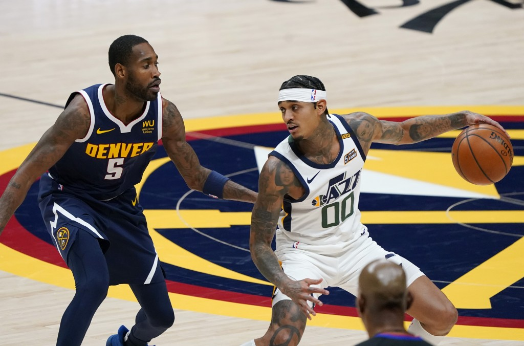 Utah Jazz guard Jordan Clarkson, right, looks to pass the ball as Denver Nuggets forward Will Barton defends in the first half of an NBA basketball ga...