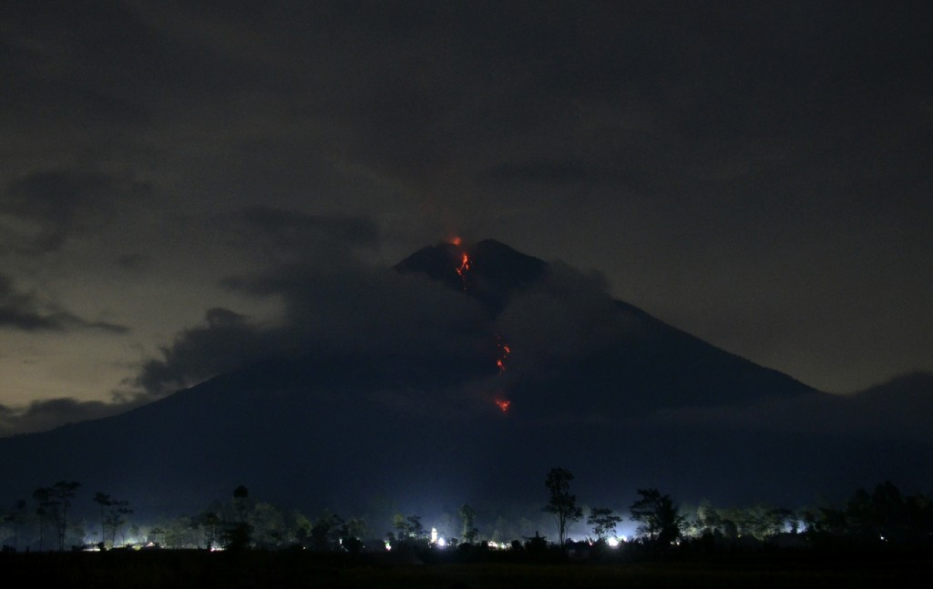 Hot lava flows from the crater of Mount Semeru as its activity continues in this photo taken with slow shutter speed in Lumajang, East Java, Indonesia...