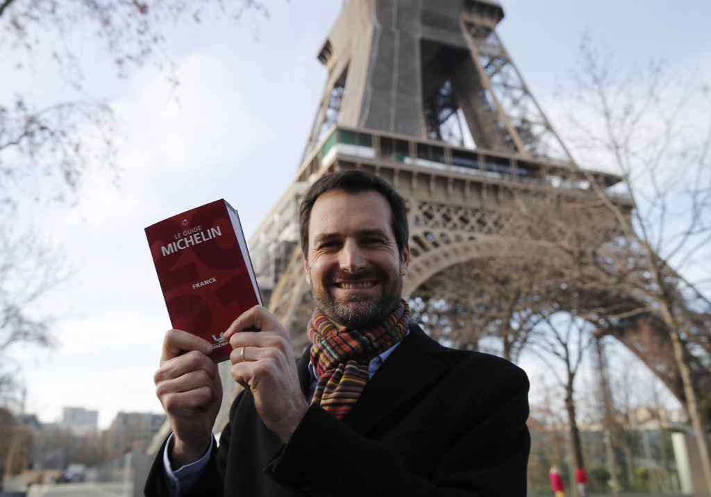 Gwendal Poullennec, head of Le Guide Michelin, poses outside the Eiffel Tower with the 2021 edition Monday, Jan. 18, 2021 in Paris. Michelin will late...