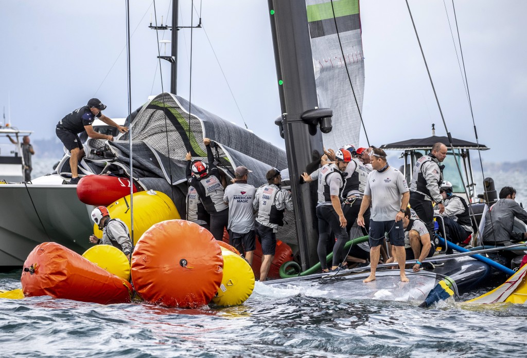 Crew from the United States' American Magic boat Patriot and Team New Zealand attempt to keep Patriot afloat after it capsized during its race against...
