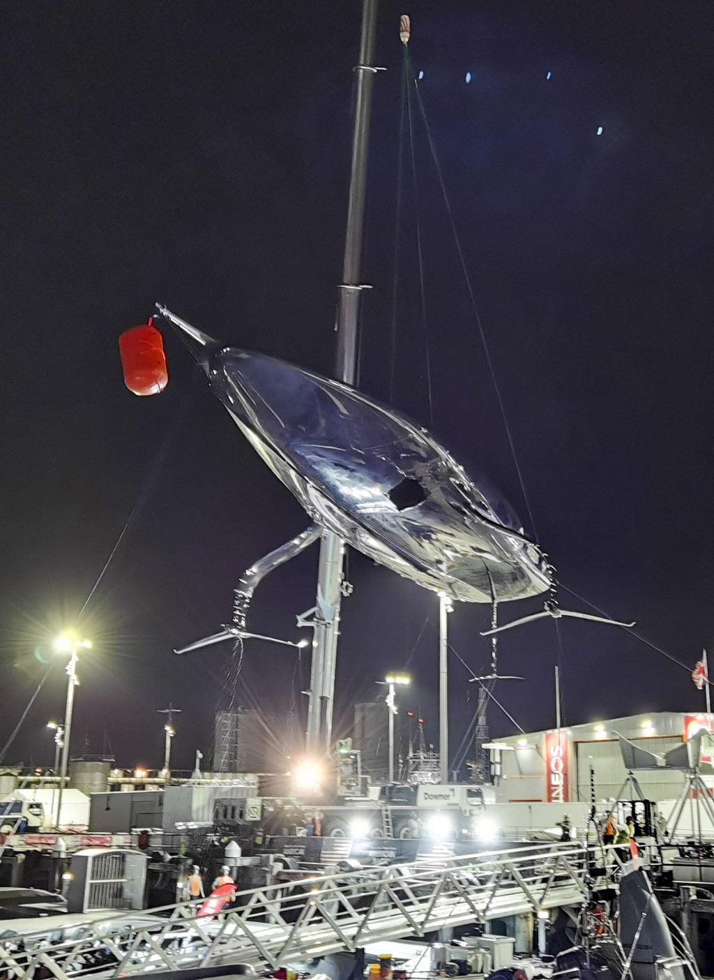 United States' American Magic's damaged boat, Patriot is lifted out of the water at its team base after it capsized during its race against Italy's Lu...