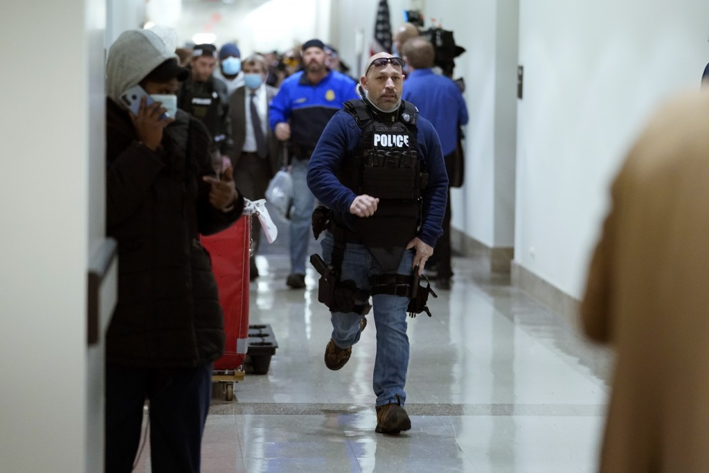 FILE- In this Jan. 6, 2021, file photo people run in the halls as rioters try to break into the House Chamber at the U.S. Capitol in Washington. (AP P...