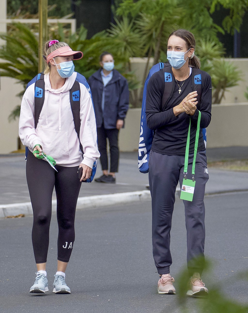 Unknown tennis players are escorted to their training session in Melbourne, Australia, Monday, Jan. 18, 2021.The number of players in hard quarantine ...