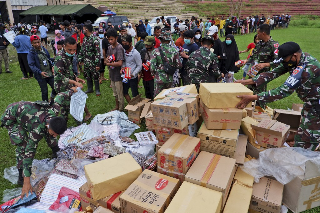 Indonesian soldiers distribute relief goods for those affected by the earthquake at a stadium in Mamuju, West Sulawesi, Indonesia, Sunday, Jan. 17, 20...