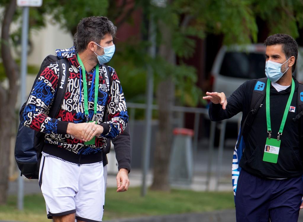 Italian tennis player Simone Bolelli, left, and Argentina's Maximo Gonzalez are escorted to their training session in Melbourne, Australia, Monday, Ja...