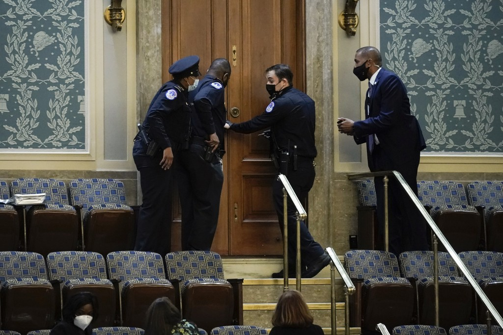 FILE - In this Jan. 6, 2021, file photo U.S. Capitol Police secure a door as rioters try to break into the House Chamber at the U.S. Capitol in Washin...