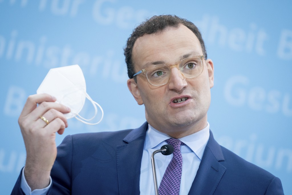 German Health Minister Jens Spahn shows his FFP2  face mask during a press conference in Berlin, Germany, Monday, Jan. 18, 2021 on the nationwide geno...