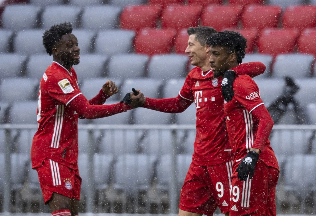 Alphonso Davies, Robert Lewandowski and Kingsley Coman of Munich, from left, celebrate the opening goal during the Bundesliga soccer match between Bay...